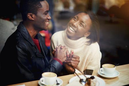 Ver a través de la ventana de alegres amantes felices disfrutando de ocio mientras está sentado en el bar en un día frío de invierno, joven negro y mujer con hermosas sonrisas en las caras que se divierten durante el descanso en la cafetería Foto de archivo