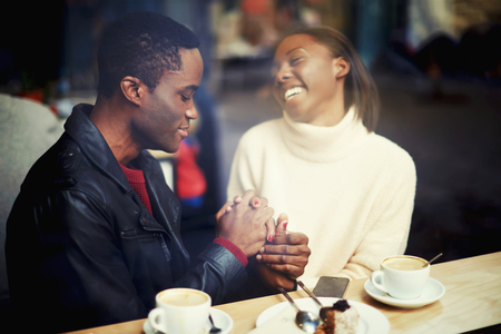 having fun in winter time: Happy black man and woman having fun time together while get warm in restaurant after strolling in cold winter day, cheerful woman sitting with her boyfriend in modern cafe bar during coffee break