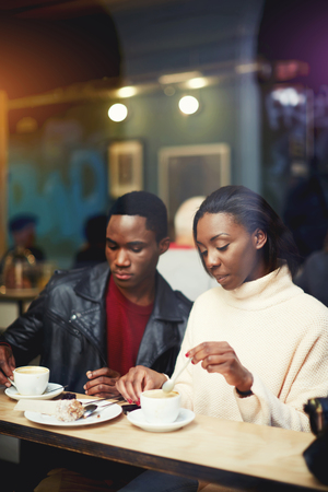 to get warm: Two young friends having joint lunch in restaurant during work break, students relaxing in cafe after lectures in University, beautiful black couple get warm in coffee shop after strolling in cold day