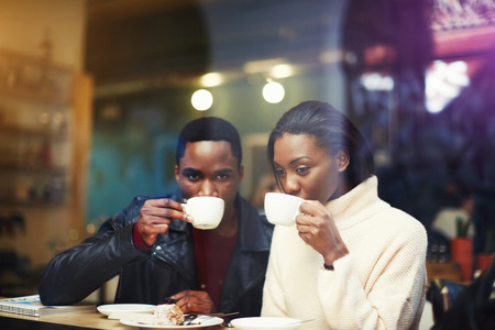 dark skinned: Black man and woman best friends drinking hot cappuccino while get warm together after walking outdoors in cold winter day, two dark skinned people relaxing in coffee shop during morning breakfast Stock Photo
