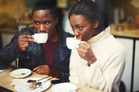 dark skinned: Young dark skinned man and woman drinking coffee while sitting together in modern cafe in cold winter day, two friends enjoying hot beverages in cozy restaurant while resting after walking outdoors
