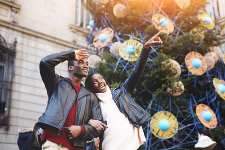 having fun in winter time: Happy dark skinned couple having fun during winter vacation, beautiful woman pointing with her finger something interesting, young lovers standing against Christmas tree with decorations on big square Stock Photo