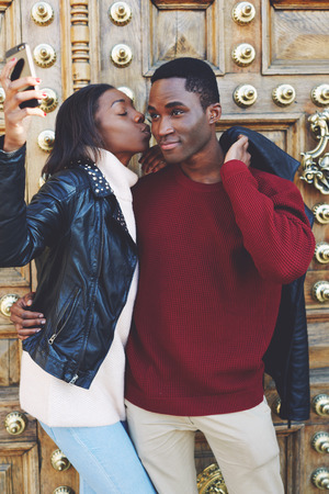 dark skinned: Young woman kissing her boyfriend on the cheek while making self portrait with smart phone digital camera, dark skinned lovers photographing themselves on cell telephone while standing outdoors