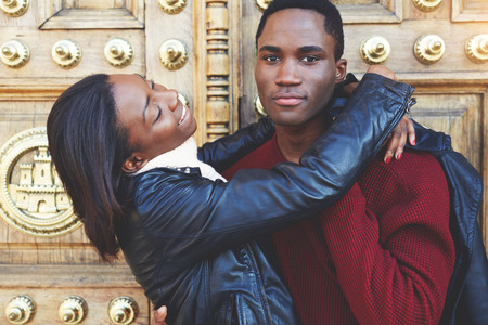 having fun in winter time: Young happy woman hug her boyfriend while posing outdoors during their winter weekend, dark skinned couple having fun while standing outdoors against vintage door, two friends enjoying recreation time