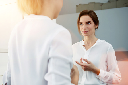 formal wear: Female entrepreneur dressed in formal wear having conversation with partner during break, young woman employee tells something about work to her colleague while standing in modern office interior