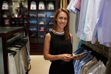 彼女のファッションのブティック、トレンディなショップでの仕事のための仕事日の間にタッチパッドを使用して豪華な女性経営者に立っている間デジタル タブレットを保持する美しい笑顔で若い実業家の肖像画 写真素材