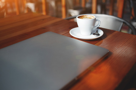 netbook: Closed laptop computer and cup of hot cappuccino lying on a wooden table in contemporary coffee shop interior, portable net-book with space for your brand, electronic business remote job via internet