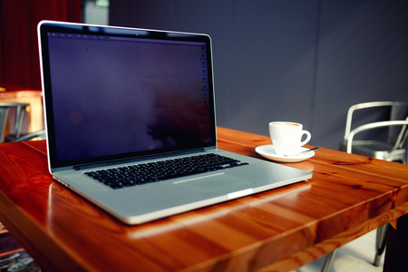 netbook: Portable laptop computer and cup of coffee lying on a wooden table in cafe bar interior, open net-book with copy space screen for your information content or text message, freelance work via internet