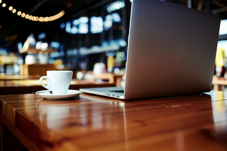 Laptop computer and cup of hot cappuccino lying on wooden table in contemporary cafe bar interior,open portable net-book with copy space for your brand, electronic business distance work via internet Stock fotó