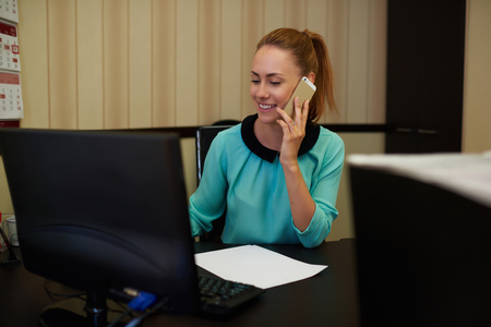 well dressed girl: Half length portrait of elegant businesswoman sitting at office table while talking on her mobile phone, attractive young female working on pc computer while having call smart-phone conversation