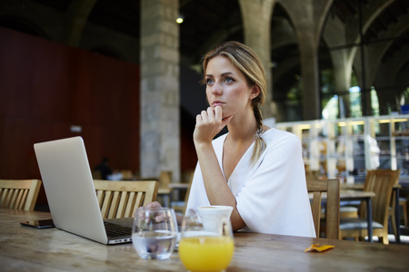 education in sweden: Portrait of a young women thinking about something while sitting front portable laptop computer in modern cafe interior, beautiful dreamy female taking break between work on net-book during breakfast Stock Photo