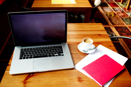 netbook: Open net-book with copy space screen for your information content or text message, electronic business distance work via internet, laptop computer and notepad with sheet of paper lying on a table