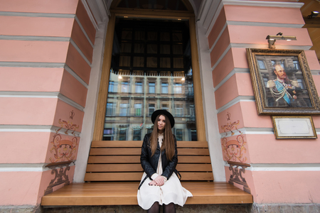 prettiness: Portrait of a young pretty glamorous woman posing while sitting on a wooden bench near historic building, beautiful female tourist with cool style relaxing after strolling in urban setting Stock Photo