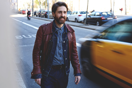 half dressed: Half length portrait of a smiling handsome bearded man dressed in cool clothes walk in urban setting in autumn day, adult beautiful male with trendy look standing on road while waiting a car or bus