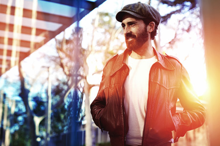 half dressed: Half length portrait of an adult bearded hipster man dressed in classy stylish clothes waiting for someone on the street, beautiful male with trendy look standing in urban setting in autumn day Stock Photo