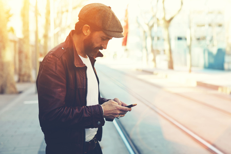 half dressed: Half length portrait of bearded male with retro style using cell telephone while standing in urban setting, man dressed in stylish clothes chatting on smart phone during walking in cool spring day Stock Photo