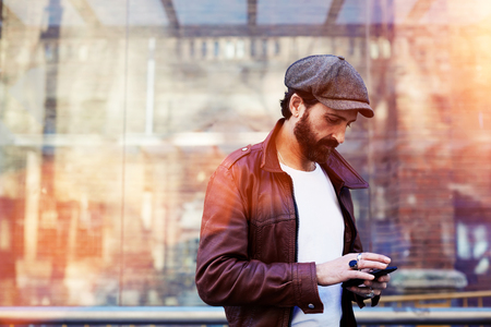 half dressed: Half length portrait of stylish men chatting on his cell telephone while standing in urban setting, hipster male with dressed in trendy clothes reading message on mobile phone during walk in cool day