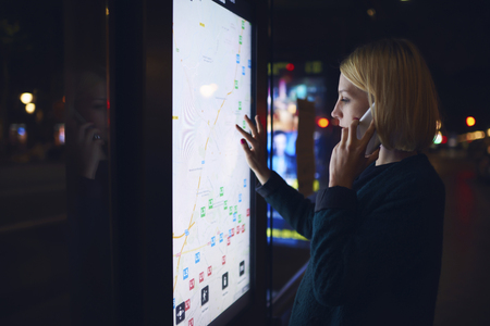 remittances: Young woman having a telephone conversation while touching digital display of smart modern bus station, charming female using city computer for touristic information while talking on mobile phone Stock Photo