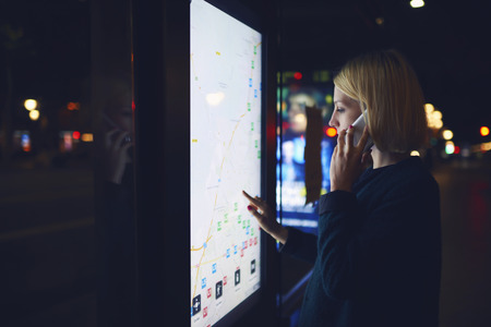 Young female tourist talking on mobile phone while looks at map of the city on an electronic bulletin board, woman calling with cell telephone while watching movement of buses standing at a stop