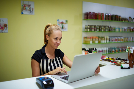 seller: Young female consultant using net-book to check for spa products while standing in pharmacy interior, attractive woman seller reading something on laptop computer during work day in cosmetic store Stock Photo