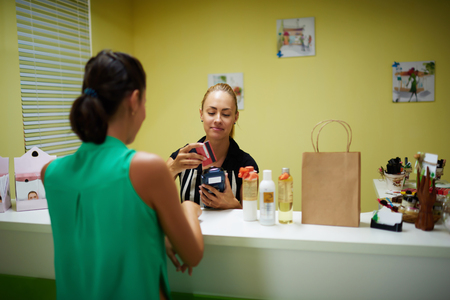 calculated: Young beautiful female prosperous seller conducted credit card by terminal, woman buyer calculated for purchases in cosmetic store, girl consultant services a client while standing in pharmacy