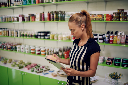 verifying: Young beautiful female consultant checks the quality of spa goods verifying information on digital tablet, woman owner using touch pad for work while standing in cosmetics store or pharmacy interior