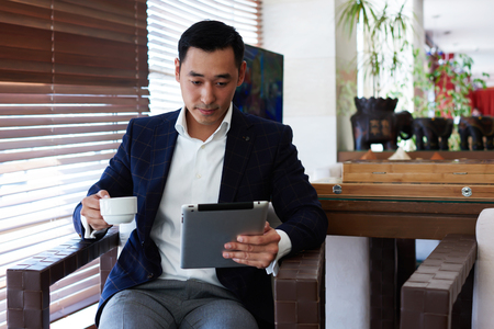 economist: Portrait of an Asian man intelligent lawyer reading electronic book on touch pad during coffee break in cafe, male purposeful economist watching news on digital tablet while sitting in modern interior