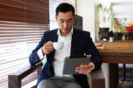 formal wear: Portrait of young man entrepreneur in formal wear enjoying coffee while reading news on digital tablet, successful male ceo dressed in luxury suit watching something on touch pad while sitting in cafe