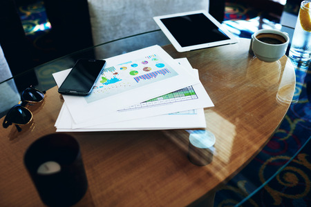 capital gains: Digital tablet and mobile phone with copy space screen for your information or promotional content lying near paper documents, touch pad and cell telephone on a glass table in modern interior
