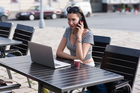 sidewalk talk: Young woman talking on smart phone while sitting at the table with open laptop computer in sidewalk cafe, attractive female calling with cell telephone while resting after work on portable net-book