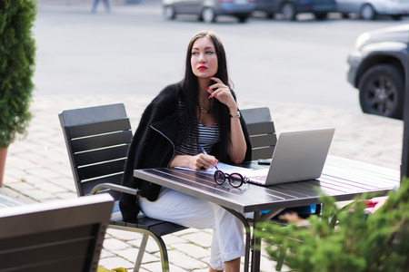 coursework: Portrait of a dreamy woman sitting at the table with paper documents and laptop computer in sidewalk cafe, attractive female thinking about something while resting after work on portable net-book Stock Photo