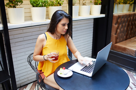 netbook: Young female successful freelancer using laptop computer for distance work while sitting in coffee shop interior, beautiful Latin woman keyboarding on net-book while relaxing in cafe after walking Stock Photo