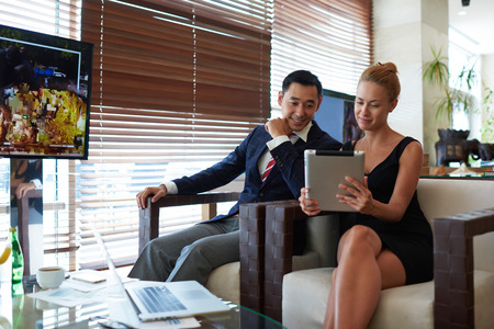 purposeful: Portrait of two professional lawyers using digital tablet while relaxing in cafe after work day, purposeful man and woman entrepreneurs watching something on touch pad during prepare for conference Stock Photo