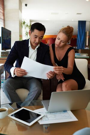 purposeful: Portrait of a purposeful business men and women watching together document papers while sitting with net-book in office interior, young prosperous two financiers discuss new ideas for joint project