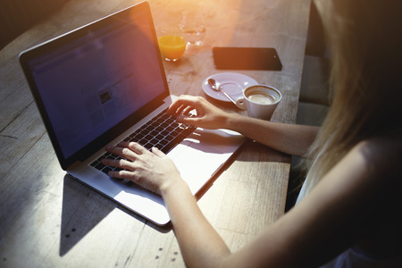 netbook: Cropped shot view of woman freelancer keyboarding on laptop computer with copy space screen while sitting in cafe, blonde female student working on net-book during morning breakfast before lectures