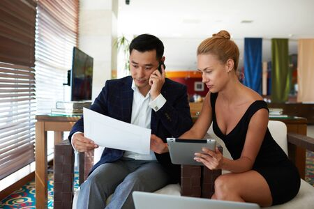 purposeful: Man purposeful managing director talk on cell telephone while his female secretary reveals paper documents with good performance, young businesswoman using touch pad during meeting with male partner