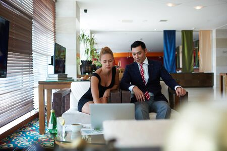 purposeful: Portrait of a two confident financiers working on laptop computer while sitting in modern office interior, young purposeful businessman and woman managers using net-book to prepare for the conference
