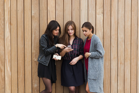 half length: Half length portrait of a young stylish hipster girls using smart phone for navigation before start their walking outside, attractive women watching something on cell telephone while standing outdoors