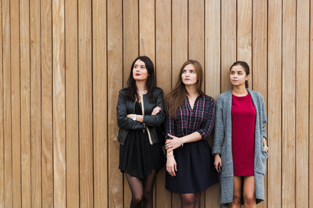 half dressed: Half length portrait of a beautiful three women with good mood dressed in trendy clothes posing against brown wall, cheerful ladies dreaming looking to the copy space area on wooden wall background