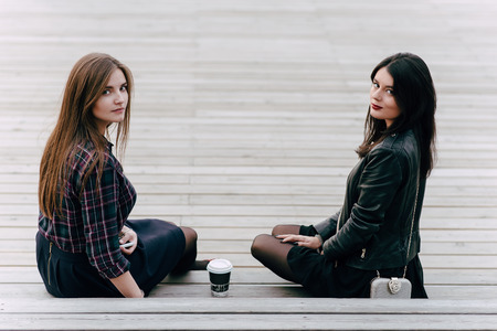 Two young charming women posing while sitting with take away coffee on a wooden stairs in the fresh air, best female friends hipster girls looking at camera with copy space area for your text