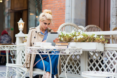 prettiness: Beautiful woman watching video on digital tablet while sitting in sidewalk cafe in spring day during free time, charming female reading something on her touch pad while she relaxing in coffee shop