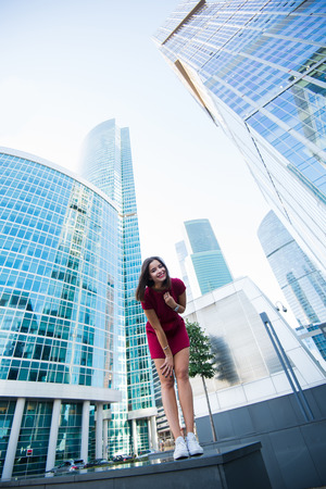 prettiness: View from below of an attractive woman with perfect figure posing against modern skyscrapers in business district, beautiful happy female standing near office buildings in summer day during free time