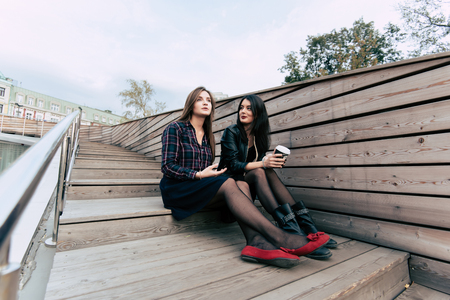 stair well: Young pretty two female hipsters talking to each other while sitting on a wooden stairs in the fresh air, couple of beautiful students girls relaxing after walking outdoors during recreation time