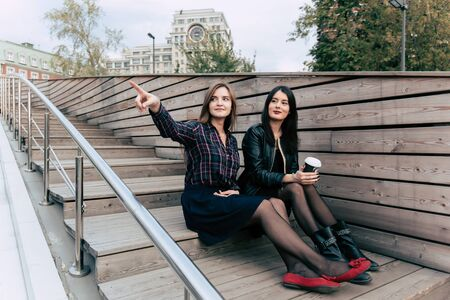 stair well: Two women best friends discussing something while sitting on a wooden stairs outdoors, young charming hipster girls look at the landscape of the city while relaxing after strolling outside in weekend