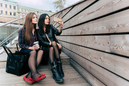 prettiness: Two women making photo on cell telephone while sitting on a wooden stairs in the fresh air, young hipster girls photographing herself on mobile camera while relaxing after walking, copy space area Stock Photo