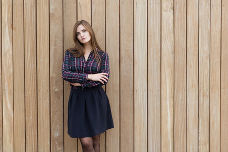 half dressed: Half length portrait of a young dreamy woman with pretty face standing with crossed arms on copy space background, beautiful European female dressed in classy trendy clothes posing against wooden wall