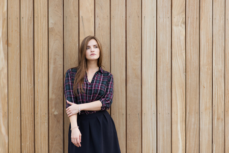 half dressed: Half length portrait of charming lady thinking about something while standing against copy space area background, young beautiful dreamy woman with good look posing for the camera against wooden wall Stock Photo