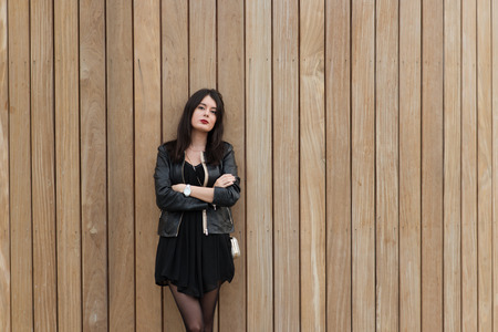 half length: Half length portrait of young European woman posing for the camera while standing against wooden wall background with copy space area, gorgeous trendy hipster girl looking at you while posing Stock Photo