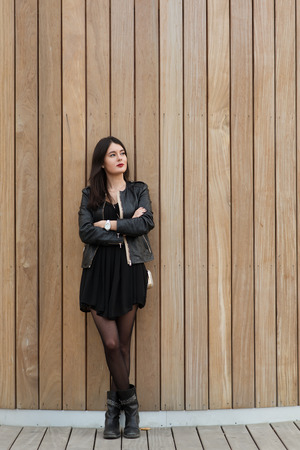 half length portrait: Half length portrait of a fashionable woman thinking about something while standing on copy space background, young beautiful dreamy female with good look posing for the camera against wooden wall Stock Photo