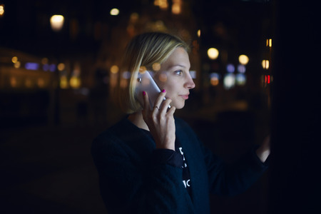 remittances: Woman calling with cell telephone and using city computer for touristic information while standing at night on the street, girl touching digital display on bus stop during mobile phone conversation